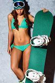 stock photo of snowboarding  - brunette sexual  fashion model woman wearing bikini and holding snowboard over gray - JPG