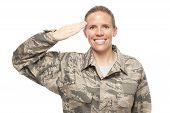 stock photo of salute  - Portrait of female airman saluting against white background - JPG