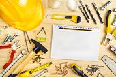 stock photo of carpentry  - Planning a Project in Carpentry and Woodwork Industry Notebook and Assorted Woodwork and Carpentry Tools on Pinewood Workshop Table - JPG