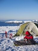 picture of thermos  - A man sits in a sleeping bag near the tent and snowshoes and drinking tea from a thermos on the background of the winter mountains - JPG