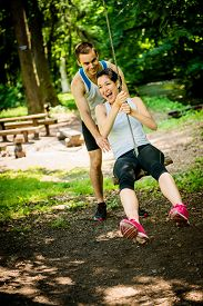 image of seesaw  - Young sport couple having fun  - JPG