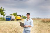foto of combine  - Young attractive farmer with laptop standing in rapeseed field truck and combine harvester working in the field in background - JPG