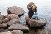 image of snickers  - Beautiful blond Caucasian teenage girl sits on coastal stones on the lake coast in Finland - JPG