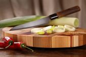 stock photo of leek  - leek cut by means of a knife rings and Chile on a chopping board - JPG