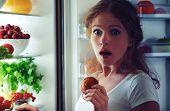 pic of sneak  - woman eats sweets at night to sneak in a refrigerator - JPG