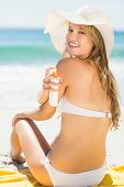 pic of sun-tanned  - Pretty blonde woman putting sun tan lotion on her shoulder at the beach - JPG