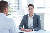 foto of conduction  - Businesswoman conducting an interview with businessman in an office - JPG