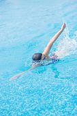 stock photo of crawling  - Young girl in goggles and cap swimming front crawl stroke style in the blue water pool - JPG