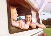 stock photo of campervan  - Beautiful young couple sitting in a camper van on a summer day - JPG