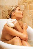stock photo of bath sponge  - Woman relaxing in a bath and washing herself by sponge - JPG