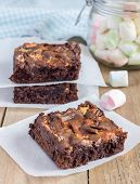 stock photo of brownie  - Homemade brownies with marshmallow on a wooden table - JPG