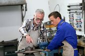 image of ironworker  - Young man in ironworks training with professional teacher - JPG