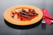 picture of black-cherry  - grilled beef meat with berries fried potatoes and cherry under sweet honey sauce on orange plate over black wooden table - JPG