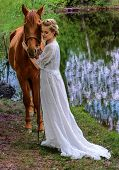 stock photo of horse face  - Woman standing with horse near lake and touching horse face with her forehead - JPG