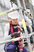 picture of scaffold  - Young woman in professional training working on scaffolding - JPG