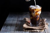 foto of tumbler  - Iced coffee in a tall glass with cream poured over - JPG