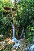 foto of observed  - Bottom view of flowing waterfall and observation terrace among trees - JPG