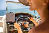 stock photo of up-skirt  - Young and pretty woman in yellow skirt and swimsuit with hat and sunglasses driving luxury yacht in the sea - JPG
