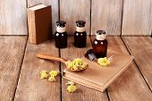 stock photo of roughage  - Old books with dry flowers and bottles on wooden background - JPG