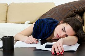 image of piles  - Female student tired and sleeping in her bed room over the notes while was studying - JPG