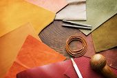 Leather craft. Colorful pieces of beautifully colored or tanned leather and leather working tools on poster