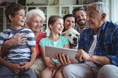 Happy multi-generation family using digital tablet in living room at home poster