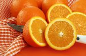 freshly sliced oranges with knife on orange colored cutting board