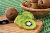 Still life image of sliced kiwi fruit on bamboo cutting board with knife.  Bowl of additional kiwi f