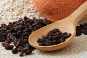 Macro still-life of raisins on large wooden spoon with decorative terra cotta bowl and oats in the background.  Shallow dof