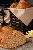 Bread Basket still-life.  Freshly baked, 9-grain, Italian bread on a ceramic cutting board with knife.  Basket of bread and sliced butter in soft focus in the background.