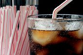 Retro image of cola on ice with old-fashioned straw dispenser.  Macro with shallow dof.  Bubbles are
