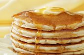 Golden pancakes with butter and warm maple syrup.  Close-up with extremely shallow dof and soft yell