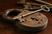 Rusty antique padlock with skeleton keys on a vintage wooden table. Macro still-life with side light