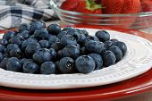 Freshly washed blueberries on a plate with strawberries in the background.  Red, white and blue color theme.  Close-up with shallow dof.
