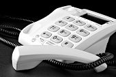 Telephone with receiver off the hook. Black and white macro image with shallow dof.  Desk surface ha