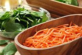 Freshly washed shredded carrots in wooden bowl with baby spinach and salad oil in the background.  Macro with shallow dof.