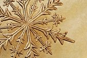 Macro image of shiny gold snowflake ornament on gold paper background.