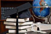 Graduation cap on stack of books with globe and bookshelves in soft focus in background.  Close-up w