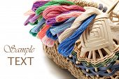 Handwoven basket with colorful skeins of thread on white background with copy space.  Macro with sha