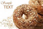 Whole grain wheat bagels with oat flakes on white background with copy space.  Macro with shallow do