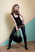 Attractive woman in black posing with bag against the wall