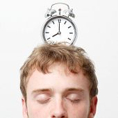 A man with an alarm clock on top of his head