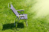 Canvas chair with shadow on a green grass