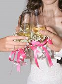 image of ecclesiastical clothing  - hands of just married with wine glasses and bows - JPG
