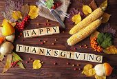 Autumn composition of vegetables, leaves, berries and wooden cubes with inscription HAPPY THANKSGIVI poster