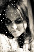 Young Girl Smiling Behind A Rainy Window In The Sun. Young Girl In The Sun By The Window With Drops  poster