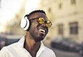 Afro man with sunglasses listening to music on his headphone on the street.