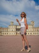A Smiling Woman Tourist With Small Orange Backpack In The Center Of Gatchina. Tourism In Europe, Wom poster