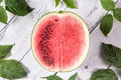 Half Of Ripe Red Watermelon Partly With And Partly Without Seeds Surrounded By Green Leaves On White poster