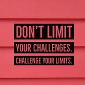 Inspirational Motivational Quote dont Limit Your Challenges. Challenge Your Limits. On Red Wooden poster